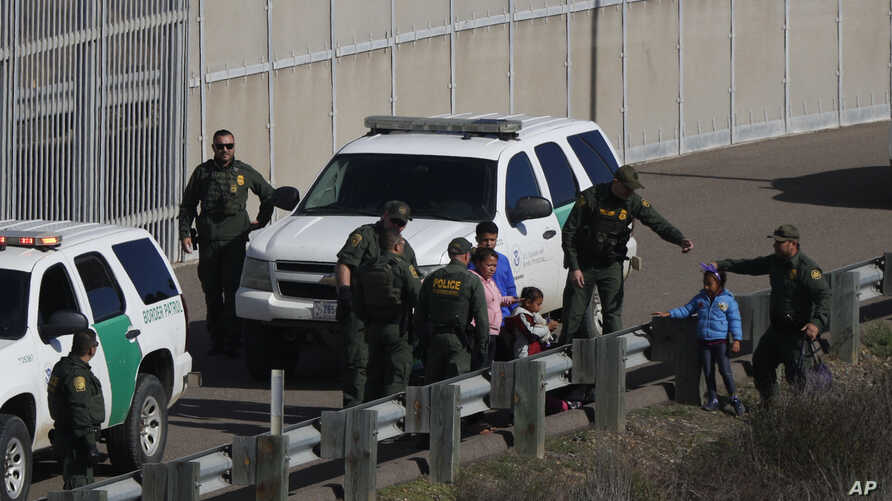 FILE -  A woman and children are ushered into cars by U.S. Border Patrol agents after crossing illegally over the border wall into San Diego, Calif., as seen from Tijuana, Mexico, Dec. 9, 2018.