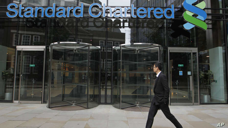 FILE - In this Aug 7, 2012, file photo a man walks by Standard Chartered bank in London. British financial services giant Standard Chartered Bank will pay $1.1 billion in fines to settle allegations by U.S. and British authorities that it attempted t...