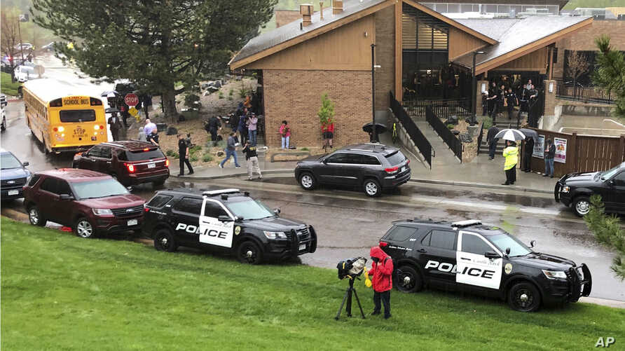 Police and others are seen outside a recreation center where students are reunited with their parents, in the Denver suburb of Highlands Ranch, Colo., after a shooting at STEM School Highlands Ranch, May 8, 2019.