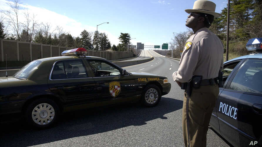 A Maryland State Trooper, who refused to give his name, stands on U.S. 50 near the Severn River bridge where traffic was stopped after an unmanned barge hit the bridge, Tuesday, March 14, 2006, in Annapolis, Md.