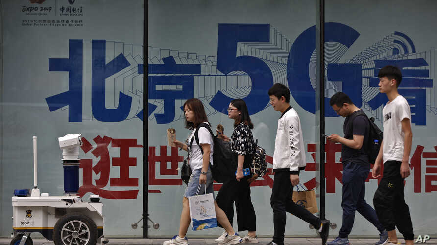 People walk toward a police robot mounted with surveillance cameras patrol past a 5G network advertisement at a shopping district in Beijing, May 15, 2019.