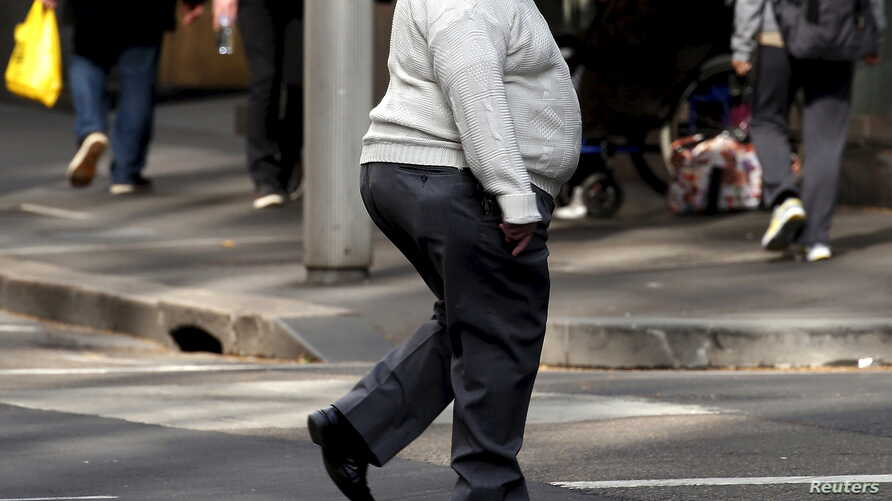 FILE - A man crosses a main road as pedestrians carrying food walk along the footpath in central Sydney, Australia.