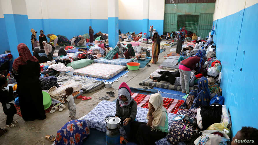 FILE - Migrants are seen at a detention center in Zawiya, west of Tripoli, Libya, April 26,2019.