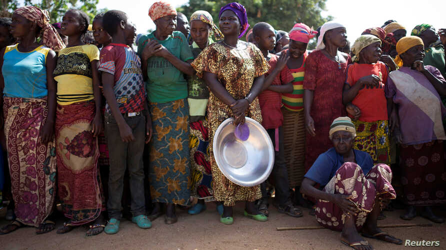 FILE - Women stand in line for food aid in the village of Makunzi Wali, Central African Republic, April 27, 2017.