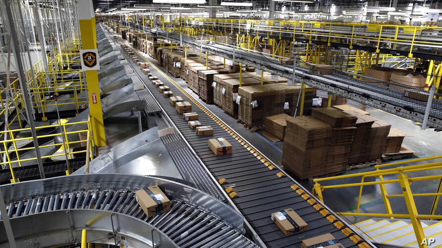 FILE - Packages ride on a conveyor system at an Amazon fulfillment center in Baltimore, Maryland, Aug. 3, 2017.