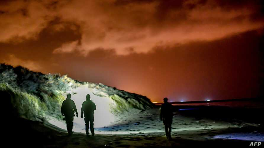 FILE - French gendarmes patrol on the beach of Oye-Plage, near Calais, northern France, Jan.  9, 2019 as they try to intercept migrants attempting to cross the Channel. British authorities intercepted 74 people on eight vessels trying to cross the En...