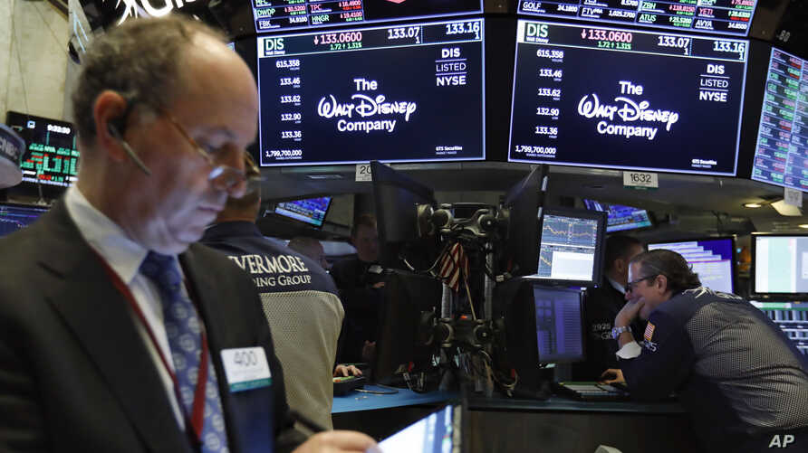 The logo for The Walt Disney Company appears above trading posts on the floor of the New York Stock Exchange, May 14, 2019. Disney is taking full control of Hulu, extending the reach of its streaming abilities.