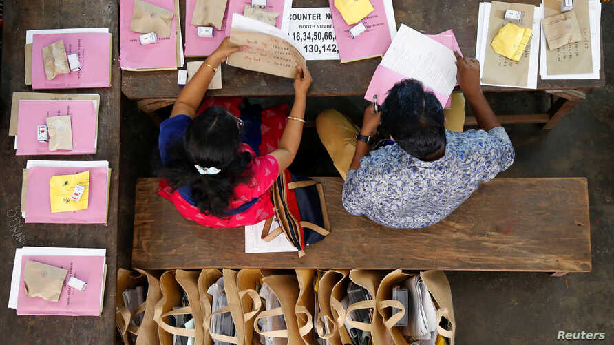 Election officials sit next to election materials to be distributed to polling stations at a distribution center, ahead of the third phase of general elections in Kochi, India, April 22, 2019.