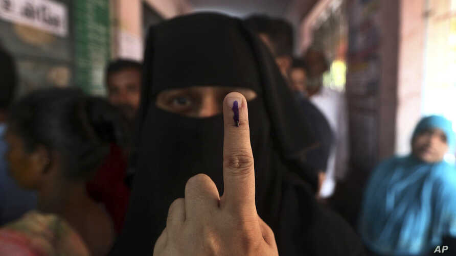 An Indian Muslim woman displays the indelible ink mark on her finger after casting her vote, outside a polling station in Chennai, India, April 18, 2019.