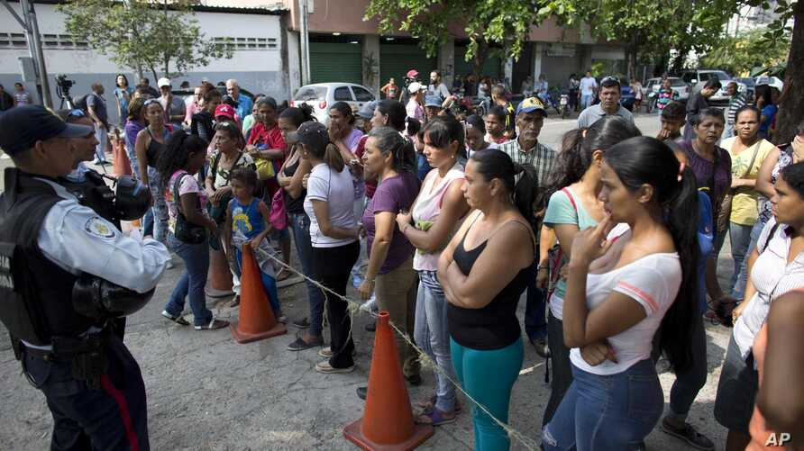 FILE - Relatives of prisoners wait to hear news about their family members imprisoned at a police station where a riot broke out, in Valencia, Venezuela, March 29, 2018.