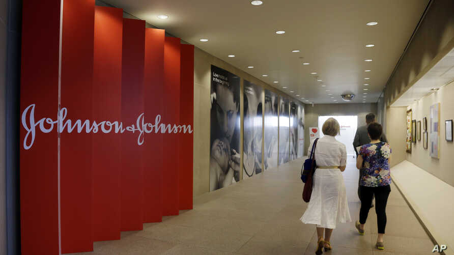 FILE - People walk along a corridor at the headquarters of Johnson & Johnson in New Brunswick, N.J.