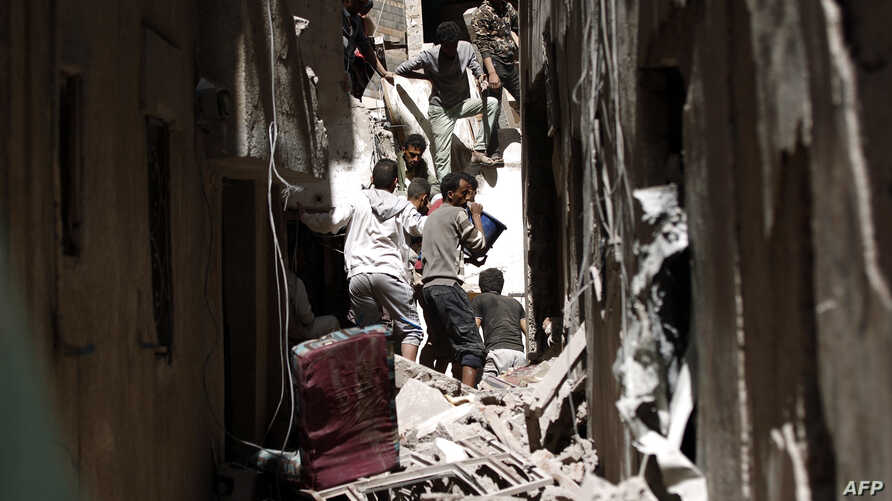 Yemenis sift through the rubble of a heavily damaged building following reported Saudi-led coalition airstrikes in the Yemeni capital Sanaa, May 16, 2019.