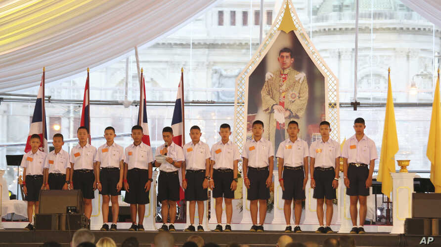 """FILE - Members of the Wild Boars, the soccer team that was rescued from a flooded cave, give thanks in front of Thailand King Maha Vajiralongkorn's image during an event titled """"United as One"""" in Bangkok, Thailand, Sept. 6, 2018."""
