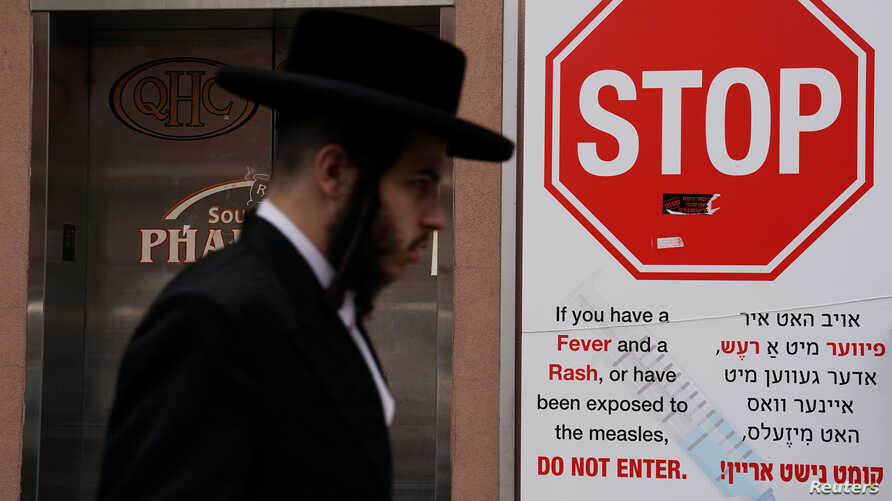 A man walks past a sign advising about a measles outbreak in the Brooklyn borough of New York, April 25, 2019.
