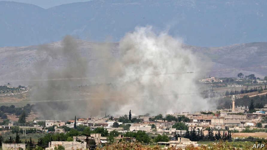Smoke billows above buildings during reported shelling by government and allied forces, in the town of Hbeit in the southern countryside of rebel-held Idlib province, Syria, May 3, 2019.