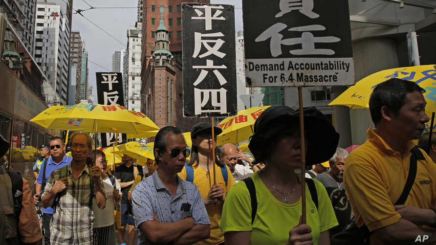 """Pro-democracy protesters carry placards with Chinese reads """"Vindicate June 4th"""" during a demonstration in Hong Kong, May 26, 2019."""