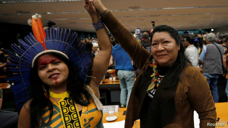 Congresswoman Joenia Wapichana, right, of the Wapixana tribe and Indigenous Leader Sonia Guajajara of the Guajajara tribe raise their hands during a meeting with congressmen in Brasilia, April 25, 2019.