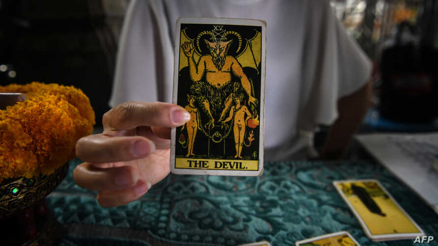 FILE - A fortune teller poses with tarot cards at a temple in Bangkok, Feb. 12, 2019.