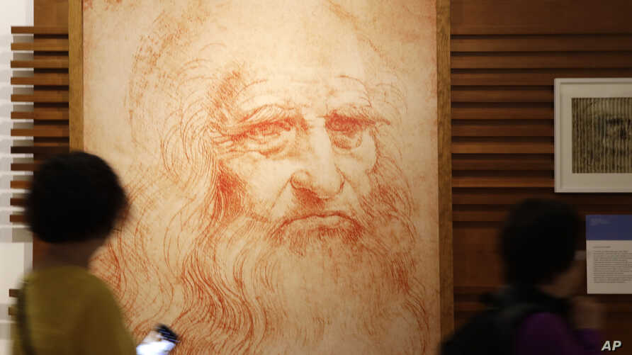 Visitors look at a portrait drawing of Italian Renaissance painter, scientist and inventor Leonardo Da Vinci during a permanent exhibition on Da Vinci, on the exact day commemorating the 500th anniversary of his death, in Rome, Thursday, May 2, 2019....