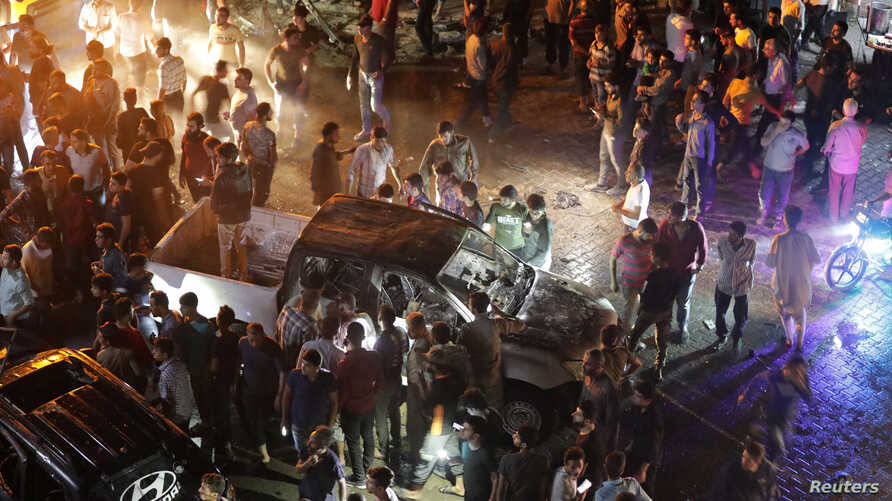 People are seen gathered at the site of a car bomb blast in Azaz, Syria, June 2, 2019.