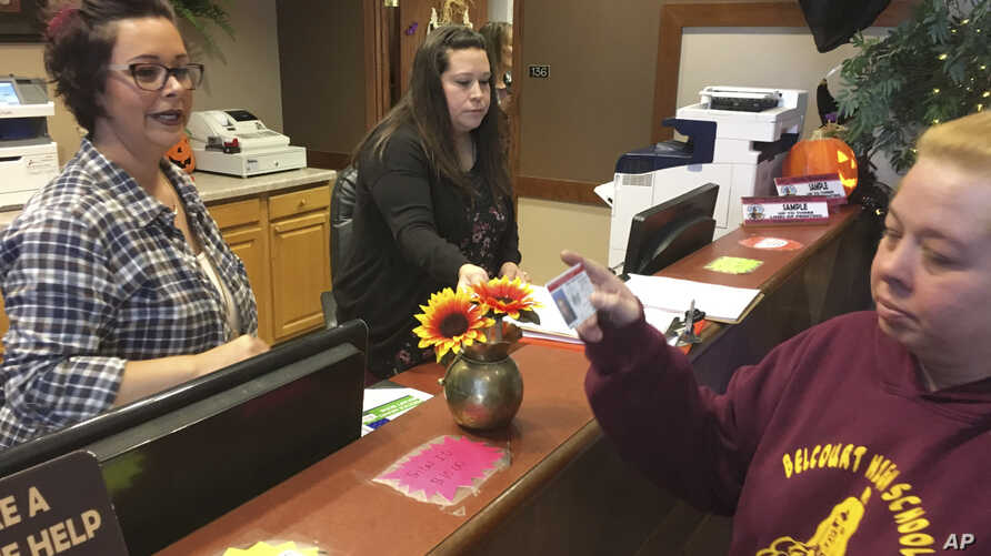 FILE - Delaine Belgarde, right, shows the new Turtle Mountain Band of Chippewa identification card she received free of charge, in Belcourt, N.D., Oct. 24, 2018. Another American Indian tribe in North Dakota is challenging the state's voter identific...