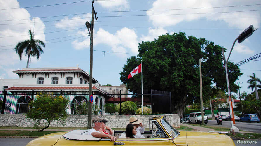 Tourists riding in a vintage car pass in front of Canada's Embassy in Havana, Cuba, May 9, 2019.