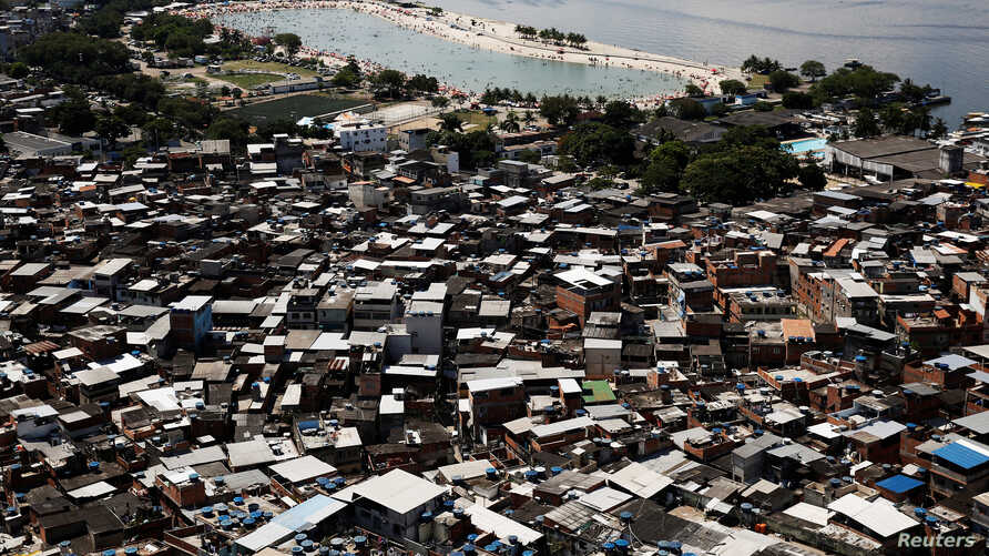FILE - An artificial pond known as piscinao, or big pool, is seen next to the Mare slums complex, in the northern suburbs of Rio de Janeiro, Brazil, Jan. 15, 2017.