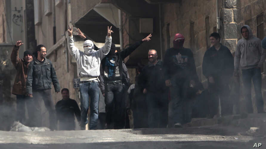 Anti-Syrian government protesters flash Victory signs as they protest in the southern city of Daraa, Syria, March 23, 2011.