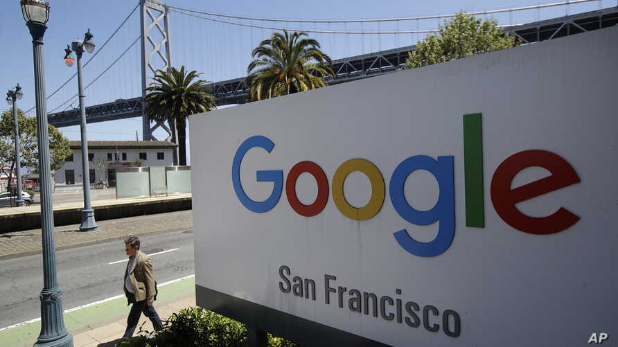 man walks past a Google sign outside with a span of the Bay Bridge at rear in San Francisco, May 1, 2019.