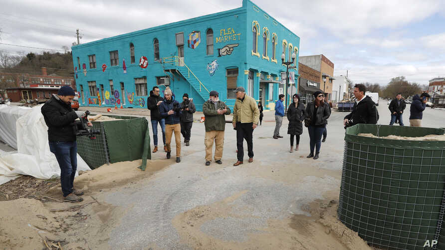 FILE - Jay Inslee, center, governor of the U.S. state of Washington and 2020 Democratic presidential candidate tours flood damage, in Hamburg, Iowa, April 12, 2019.