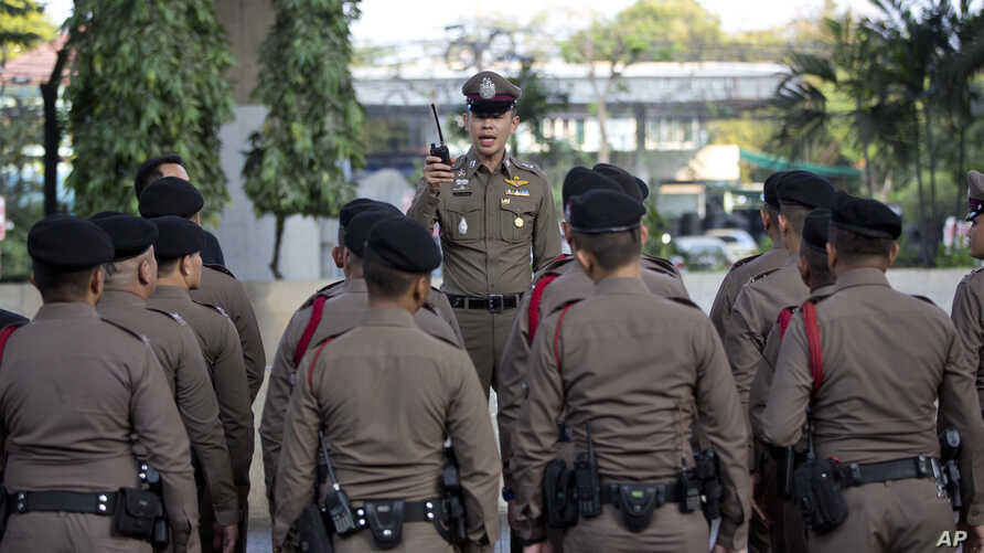 FILE - A police officer briefs others in Bangkok, Thailand, March 24, 2019. Three Thai activists remain missing after having been accused of insulting the country's monarchy.