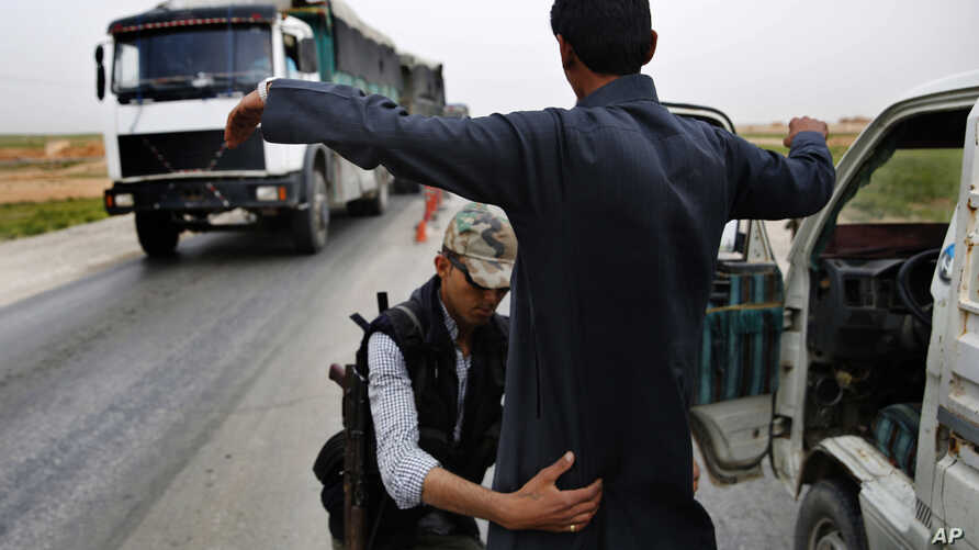 In this March 28, 2018 photo, a Kurdish policeman checks an Arab Syrian man at a checkpoint controlled by The U.S.-backed Syrian Democratic Forces, SDF, on a highway in Hassakeh province.