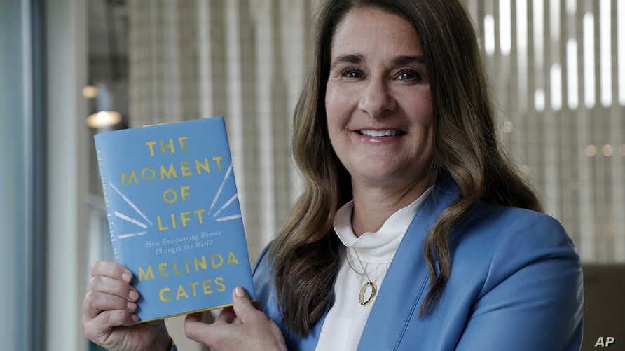 """Melinda Gates poses for a photo with her new book, """"The Moment of Lift,"""" in Kirkland, Wash., April 18, 2019. Her new book is a memoir from the former Microsoft tech business executive, outspoken feminist and public supporter of the MeToo movement."""