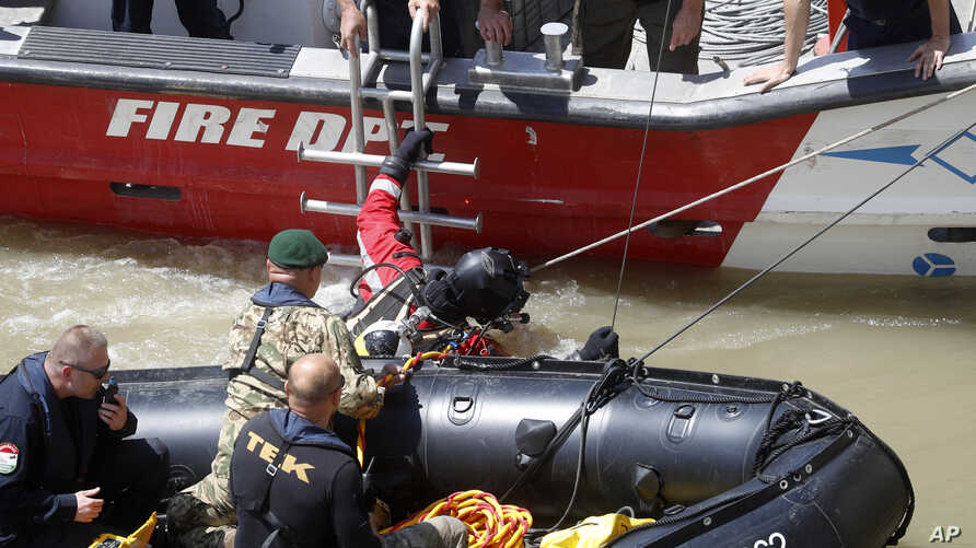 A diver prepares to dive to the wreckage under Margaret Bridge in Budapest, Hungary, May 31, 2019. Seven people are confirmed dead and seven have been rescued, while 21 people remain missing in the waters. A South Korean group on a package tour of Europe — including 30 tourists, two guides and a photographer— were on an hour-long sightseeing tour of Budapest when their boat collided with a Viking cruise ship during a downpour Wednesday evening. (AP Photo/Laszlo Balogh)