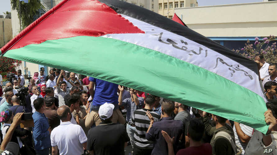 FILE - Palestinian refugees hold flags as they chant slogans during a protest in front in Amman, Jordan, Sept. 2, 2018.