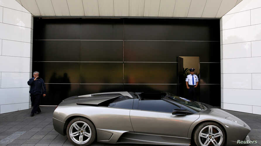 A police officer stands near a Lamborghini Murcielago 2007, part of a group of vehicles seized by the government from politicians and organized crime as part of an auction in Mexico City, May 21, 2019.