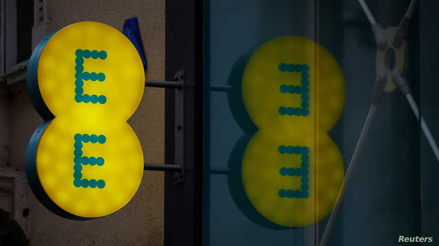 FILE - Signage is seen outside an EE mobile phone shop in Manchester, Britain, Sept, 21, 2017.