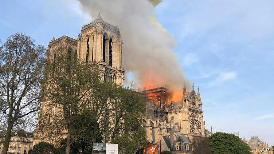 Notre Dame cathedral is burning in Paris, April 15, 2019. Massive plumes of yellow brown smoke is filling the air above Notre Dame Cathedral and ash is falling on tourists and others around the island that marks the center of Paris.