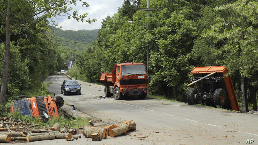 A car passes by trucks used as barricades after Kosovo police cleared the road near Zubin Potok, Kosovo,  May 28, 2019.