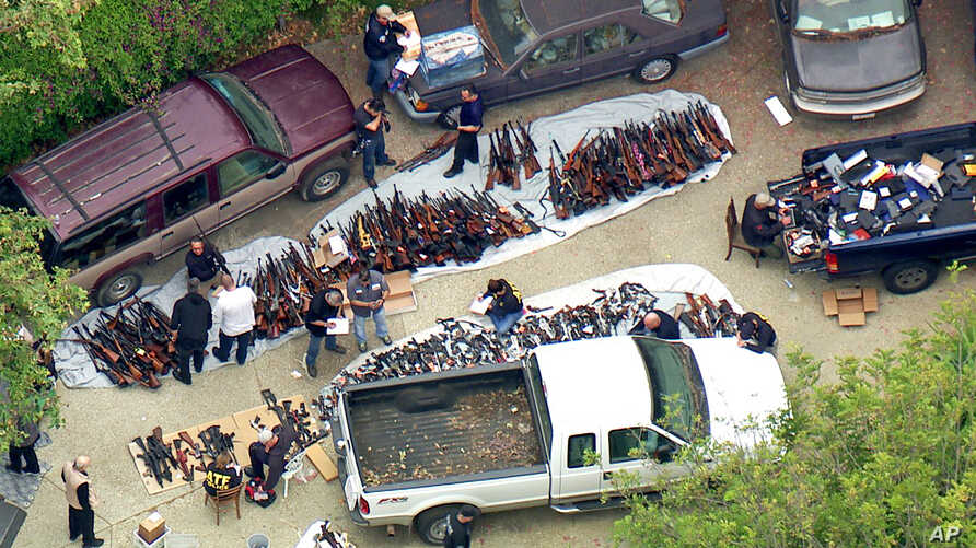 This photo from video provided by KCBS/KCAL-TV shows investigators from the U.S. Bureau of Alcohol, Tobacco, Firearms and Explosives and the police inspecting a large cache of weapons seized at a home in the affluent Holmby Hills area of Los Angeles,...