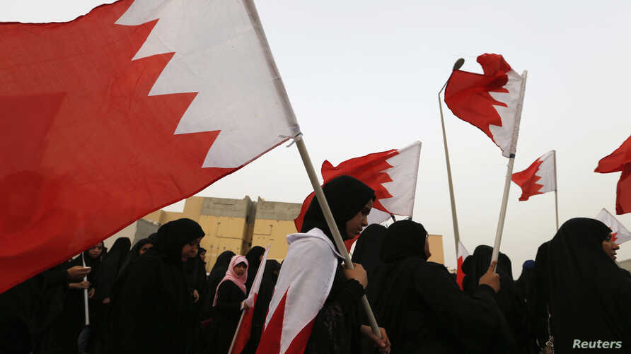 FILE - Opposition protesters, holding Bahraini flags, shout slogans during an anti-government rally in Sitra, south of Manama, June 28, 2013.