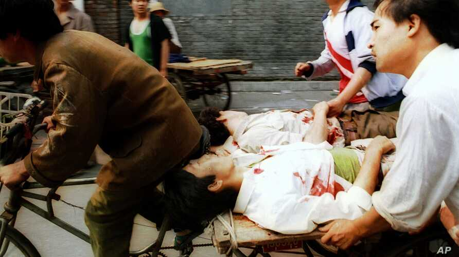 FILE - In this June 4, 1989, photo, a rickshaw driver transports wounded people, with the help of bystanders, to a nearby hospital in Beijing after they were injured during clashes with Chinese soldiers in Tiananmen Square.