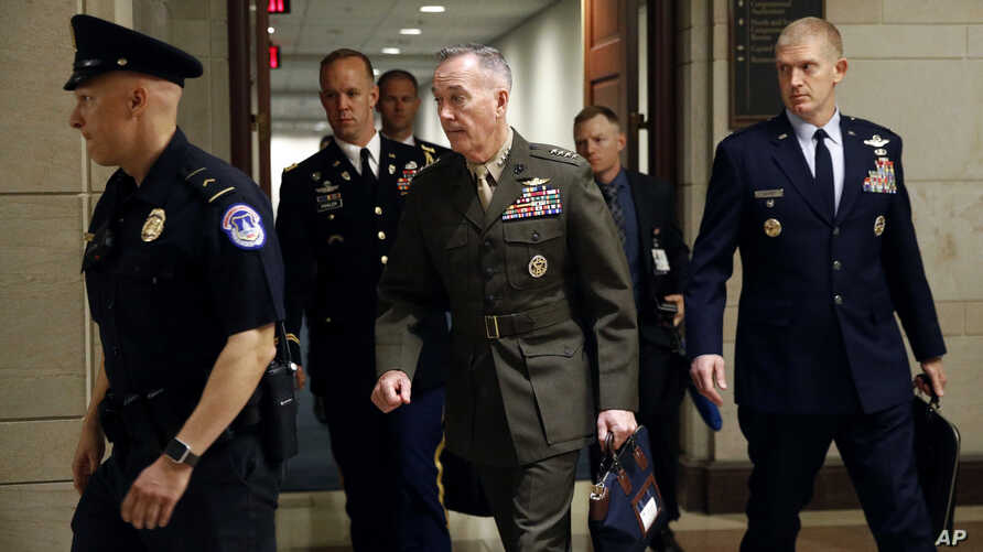 Joint Chiefs Chairman Gen. Joseph Dunford, center, walks to a classified briefing for members of the U.S. Senate on Iran, on Capitol Hill in Washington, May 21, 2019.
