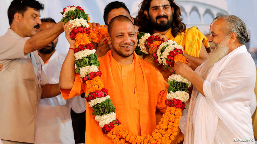 FILE - Supporters of Yogi Adityanath (C), Chief Minister of India's most populous state of Uttar Pradesh, present him with a garland on the occasion of the birthday celebration of Nritya Gopal Das, a famous Hindu priest, in Ayodhya, India, May 31, 20...