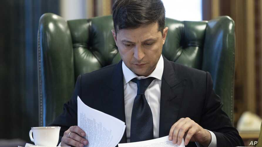 FILE - Ukrainian President Volodymyr Zelenskiy looks at documents at his office in Kyiv, Ukraine, May 20, 2019.