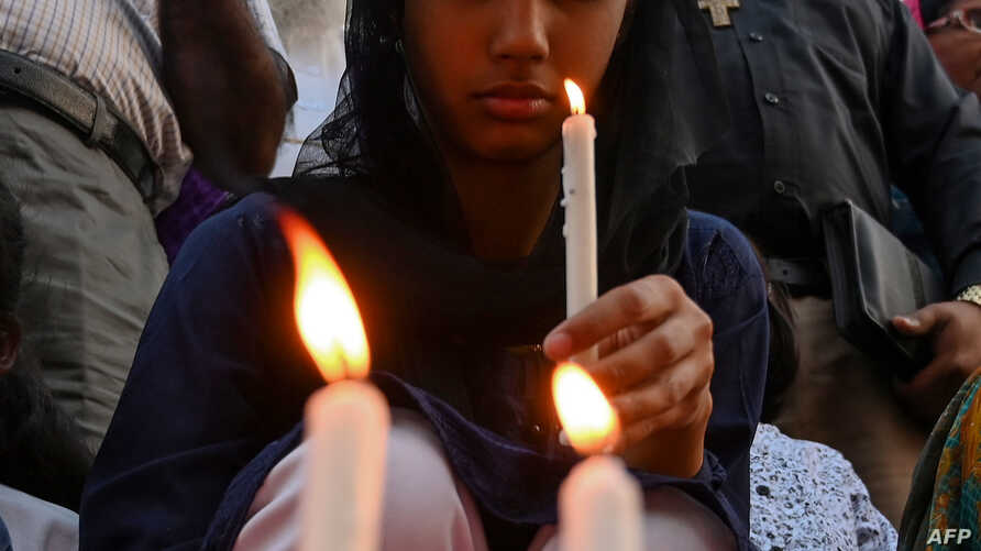 A young Pakistani Christian holds a candle to pay tribute to the Sri Lankan blasts victims during a vigil in Islamabad on April 22, 2019.