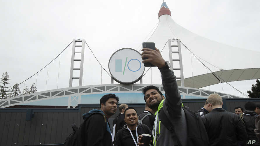 A group of attendees take photos while waiting in line for the keynote address of the Google I/O conference in Mountain View, Calif., May 7, 2019.