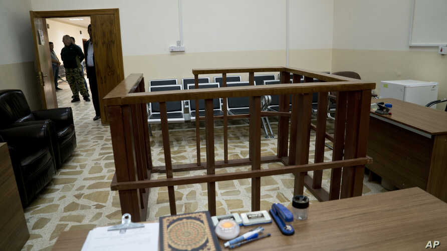 FILE - in this April 26, 2018 file photo, the defendant's cage is in the center of an empty courtroom at Nineveh Criminal Court, one of two counterterrorism courts in Iraq where suspected Islamic State militants and their associates are tried, in Tel...