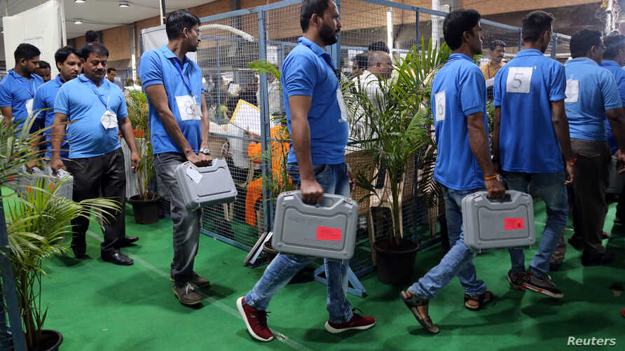 Election staff members carry electronic voting machines (EVM) at a vote counting center in Mumbai, India, May 23, 2019.