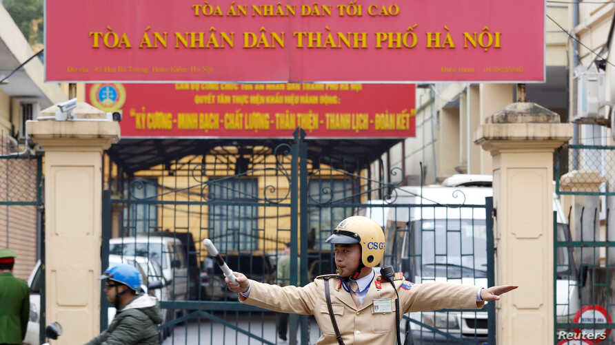 FILE - A policeman directs traffic in front of a court in Hanoi, Vietnam, Jan. 8, 2018.
